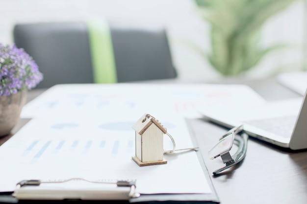不動産の概念、テーブルのホームキーと財務用紙の家モデル Premium写真