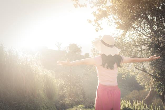 幸せな女性リラックスして、夕日に屋外に、平和で自由な女の子を楽しんで Premium写真