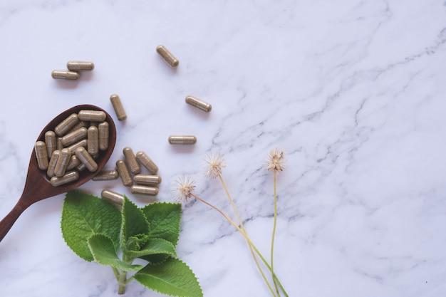 Фитотерапия в капсулах на деревянной ложке с натуральным зеленым листом на белом мраморе Premium Фотографии