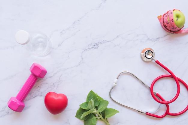 健康的な概念、赤いハートと白い大理石の背景に聴診器と青リンゴとピンクのダンベルの平干し Premium写真