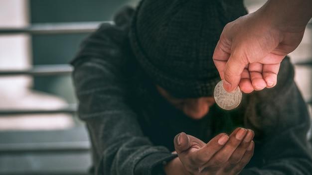 Бедный бездомный или беженец, сидящий на грязном полу и получающий деньги. Premium Фотографии
