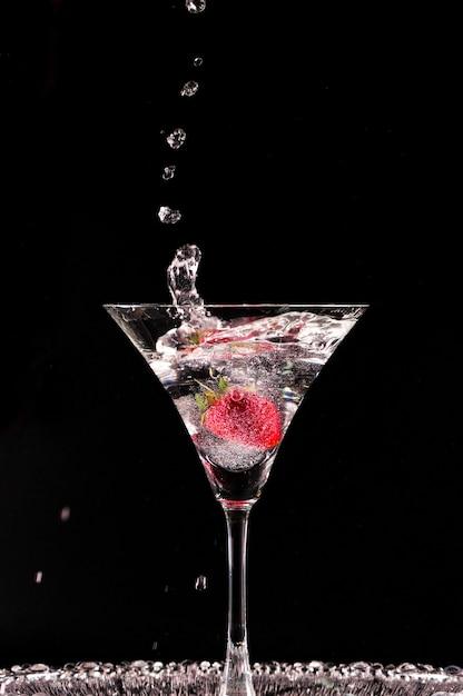 黒の背景に分離されたイチゴとカクテル。しぶきのウォッカのグラス。 Premium写真