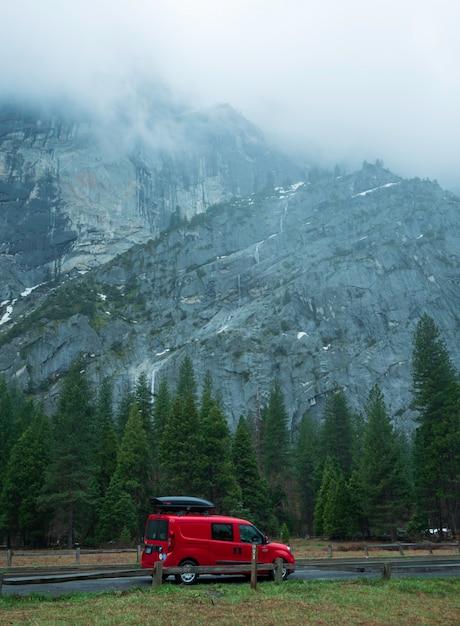 旅行者の赤い車は美しさ崖の背景を持つヨセミテ国立公園に駐車。 Premium写真