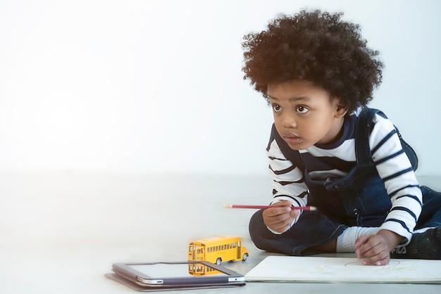 ソフトフォーカス、アフリカ系アメリカ人の少年の描画と絵画に満足 Premium写真
