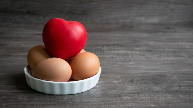 木製の床の上に皿の形の心臓の赤い球の泡を持つ卵のグループ。 Premium写真