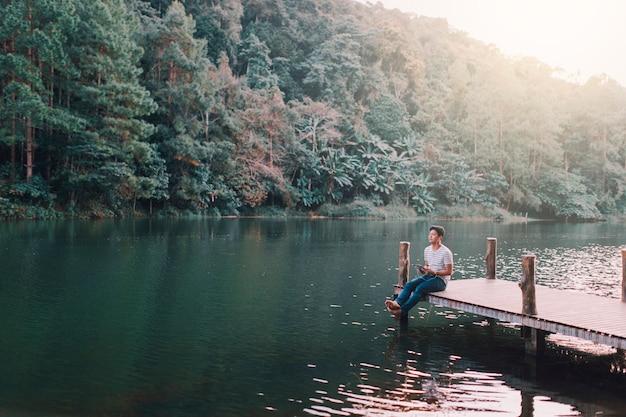 午後、湖畔の木製の橋で男性がリラックスしていた。 Premium写真