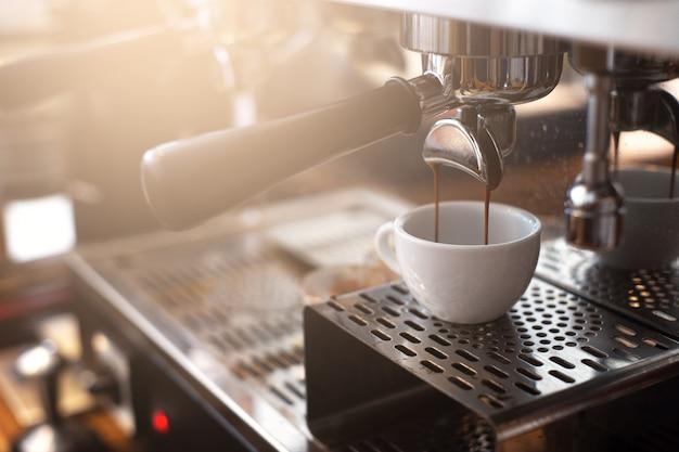 喫茶店のコーヒーメーカーからのエスプレッソ抽出 Premium写真