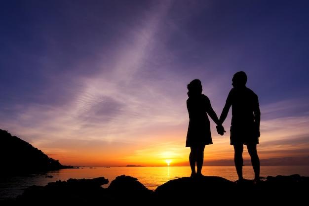 カップルのシルエットはビーチで自分の手を握る Premium写真