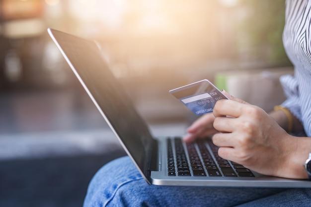 クレジットカードを保持しているとラップトップを使用して若い女性 Premium写真