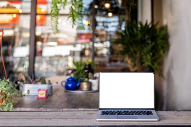 コーヒーショップの背景を持つテーブル上のラップトップ Premium写真