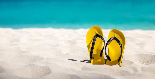 砂浜で黄色のフリップフロップが浮かんでいます。 Premium写真