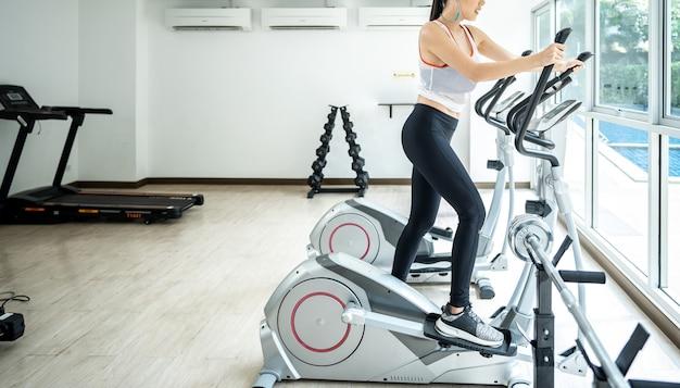 Молодые женщины занимаются спортом на велосипеде со своей подругой в тренажерном зале для фитнеса Premium Фотографии