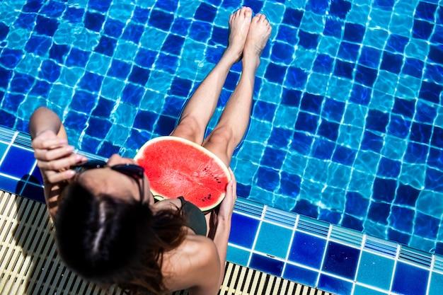 リラックスしてスイミングプールでウォーターマロンを保持している女性。 Premium写真