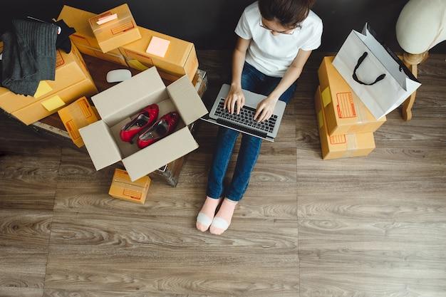 アジアのティーンエイジャーのオーナーのビジネス女性は、オンラインショッピングや販売のために家で働いています。 Premium写真