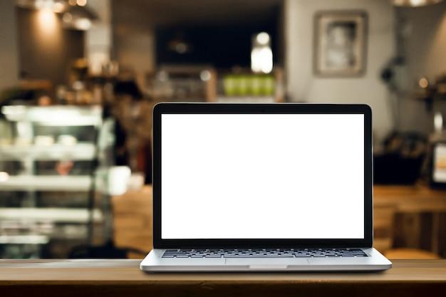 コーヒーショップの背景を持つテーブル上のラップトップ。 Premium写真