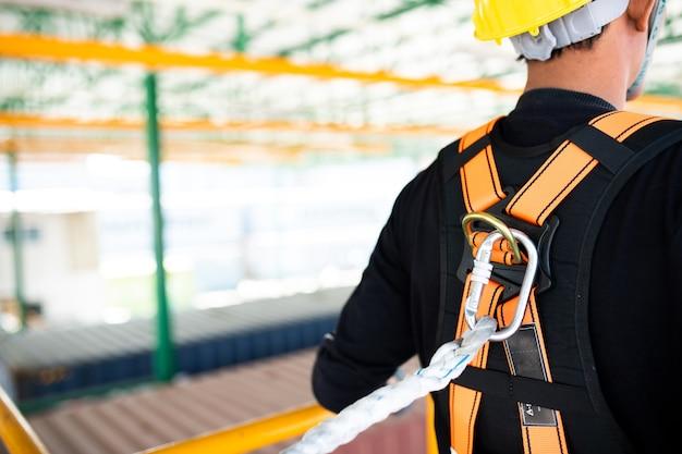 建設に取り組む安全ハーネスと安全ラインを着て建設労働者 Premium写真