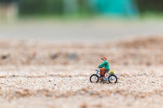 ミニチュアの人々:砂の上の自転車に乗る旅行者 Premium写真