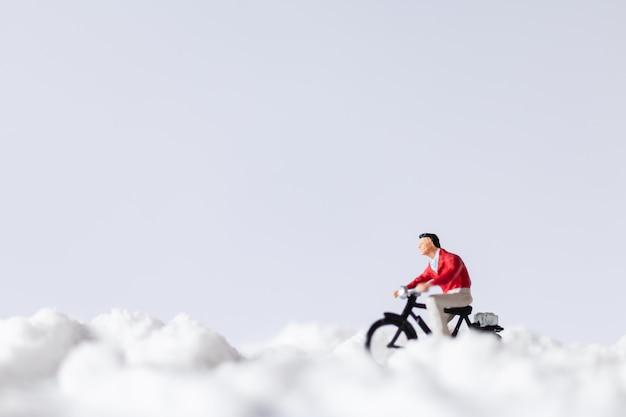 ミニチュアの人々:雪の上で自転車に乗る旅行者 Premium写真