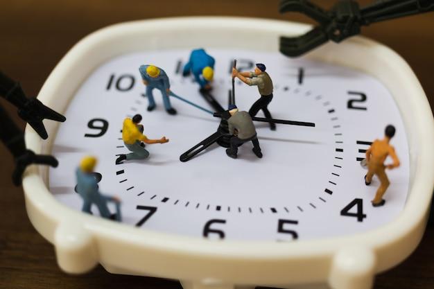 ミニチュアの人々:チームは目覚まし時計に取り組んでいます Premium写真