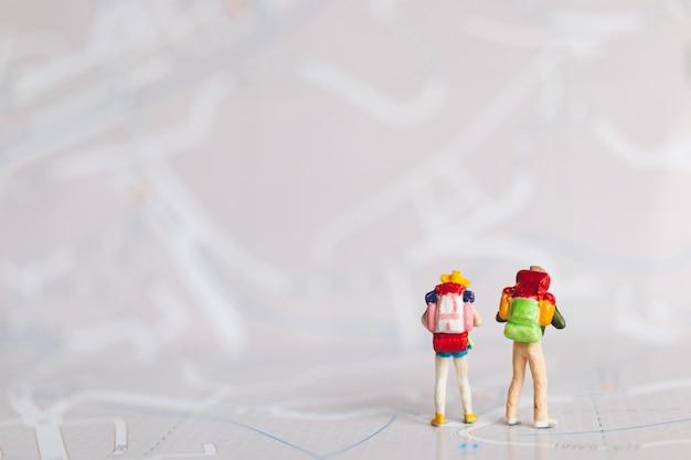 Миниатюрные люди: путешественник с рюкзаком, идущий по карте Premium Фотографии