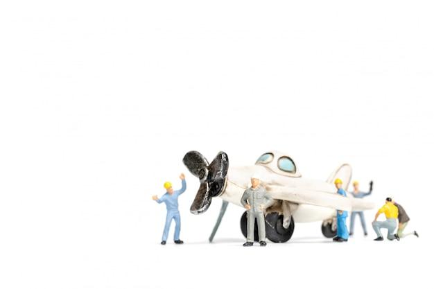 Рабочая команда ремонтирует игрушечный самолет на белом фоне Premium Фотографии