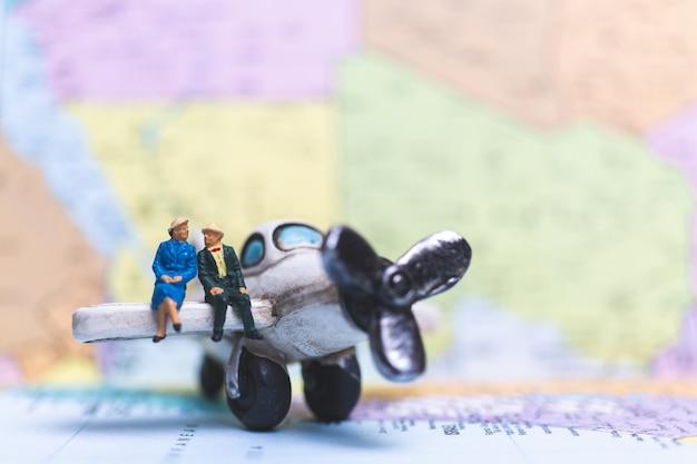 Миниатюрные люди, сидящие на самолете с фоном карты мира Premium Фотографии