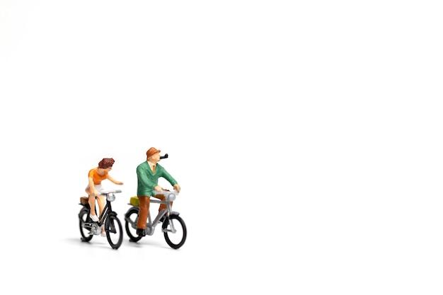 ミニチュアの人々:カップルは白い背景の上の自転車に乗る Premium写真