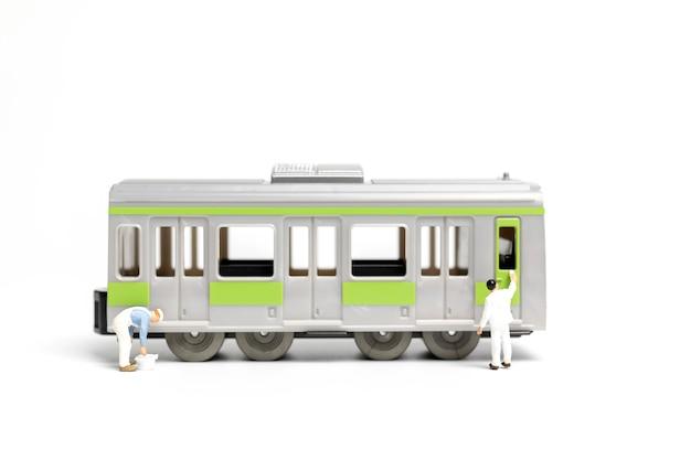 白い背景の上に電車を塗る画家 Premium写真