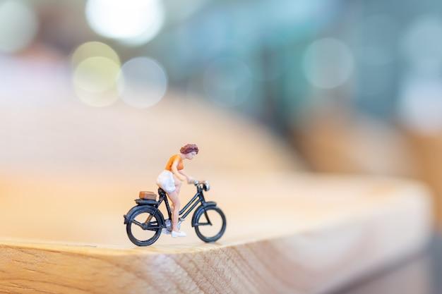 ミニチュアの人々が木の橋でサイクリング Premium写真