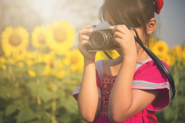 Милая маленькая девочка фотографирует с винтажной камерой в поле солнцецвета. Premium Фотографии