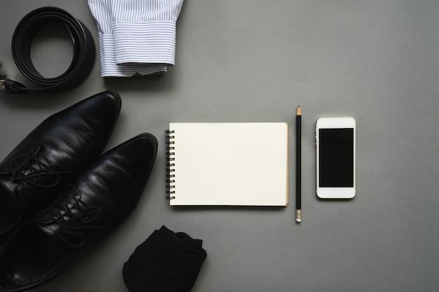 Плоский дизайн лежал бизнесмен одежды с пустой блокнот и смартфон на сером фоне Premium Фотографии
