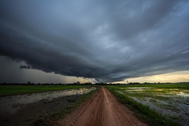 Грозовое облако приближается к местной дороге. Premium Фотографии