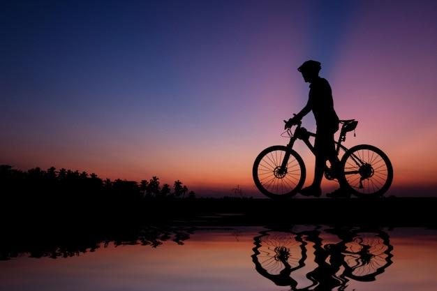 美しい日没時間にマウンテンバイクのサイクリストのシルエット。 Premium写真