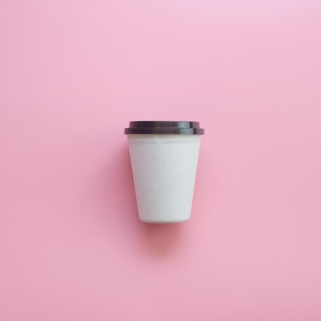 Плоский дизайн лежал чашка горячего кофе на розовой пастели. Premium Фотографии
