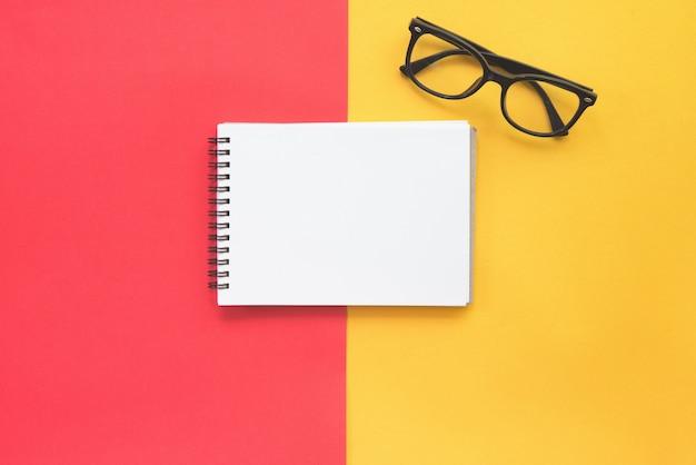 Черные современные очки и пустой блокнот на красном и желтом фоне. Premium Фотографии