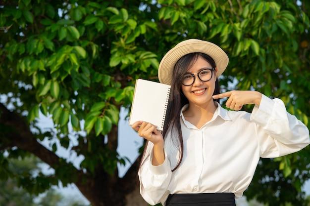 Счастливая девушка держит пустой блокнот с природой Premium Фотографии