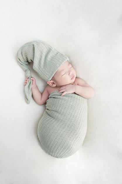ベビーベッドで寝ている幸せなかわいい赤ちゃん女の子。両親のベッドで昼寝をしている小さな子供 Premium写真