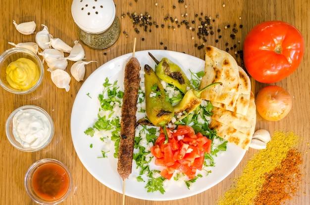 Традиция греческая лаваша с мясом, жареный картофель, помидор, лук Premium Фотографии