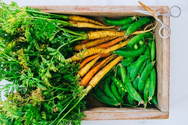 新鮮な汚れた野菜ニンジン、ビート、エンドウ豆の大理石の背景に木製の箱 Premium写真