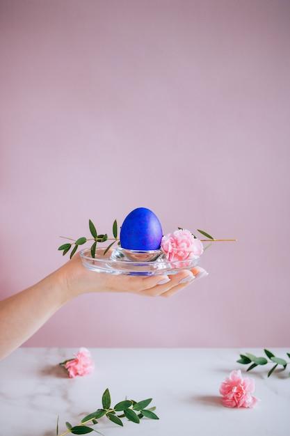 少女はスタンド、ピンクと大理石の背景、ミニマリズム、花に紫のイースターエッグを持っています Premium写真