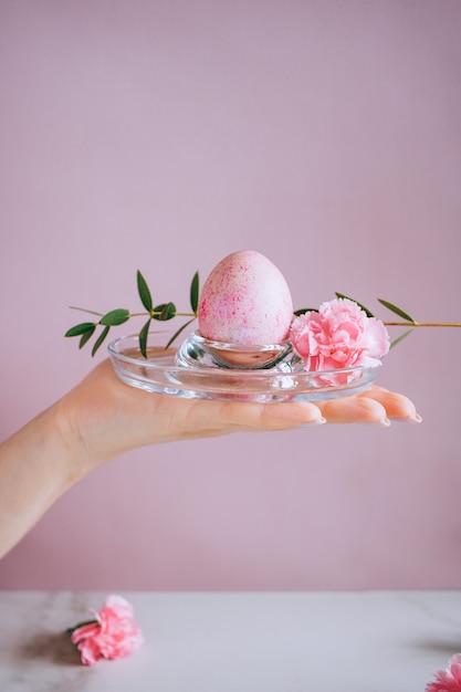 女の子はスタンド、ピンクと大理石の背景、ミニマリズム、花にピンクのイースターエッグを持っています。 Premium写真