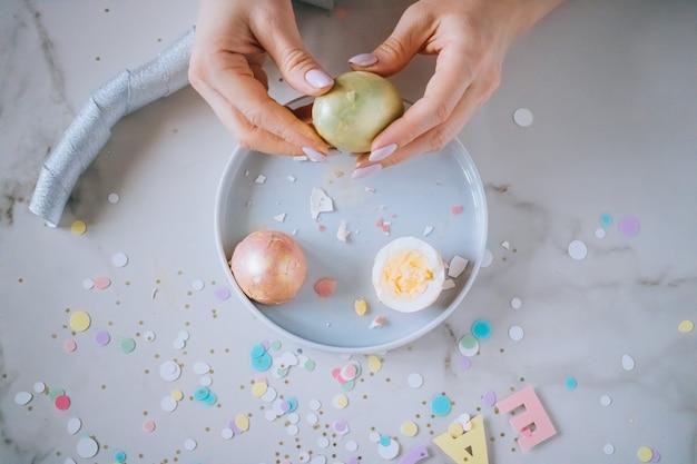 女の子は大理石の背景、紙吹雪、輝き、リボンに黄金のイースターエッグを改します。 Premium写真