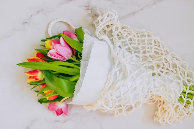 大理石の背景にエコバッグの色とりどりのチューリップの春の花束。コピースペース、フラットレイアウトの背景。 Premium写真
