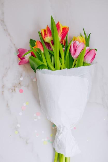 Золотая звезда украшения, яркие конфетти и розовые и красные тюльпаны на фоне мрамора Premium Фотографии