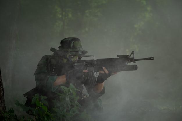 Военный таиланд: тайский солдат держит оружие в полной военной форме. рейнджерс, чтобы найти новости Premium Фотографии