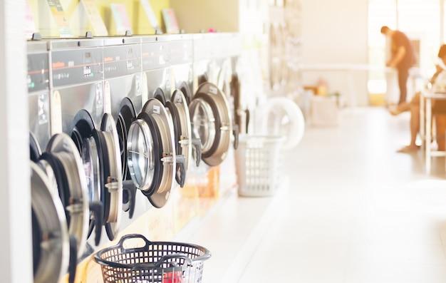 Ряд промышленных стиральных машин в прачечной самообслуживания в общественной прачечной, с прачечной в корзине, таиланд Premium Фотографии