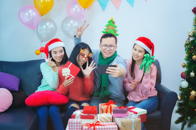 Автопортрет друзей смешанной расы: азиатские молодые улыбающиеся бородатые мужчины и красивые женщины в красной шляпе рождество позирует, празднование нового года и праздников концепции Premium Фотографии