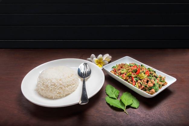 ダークブラウンのテーブルの上の白い皿にバジルの葉と豚肉の炒めご飯 Premium写真