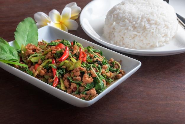 濃い茶色のテーブルの上の白い皿にバジルの葉と揚げ豚肉とご飯を閉じる Premium写真
