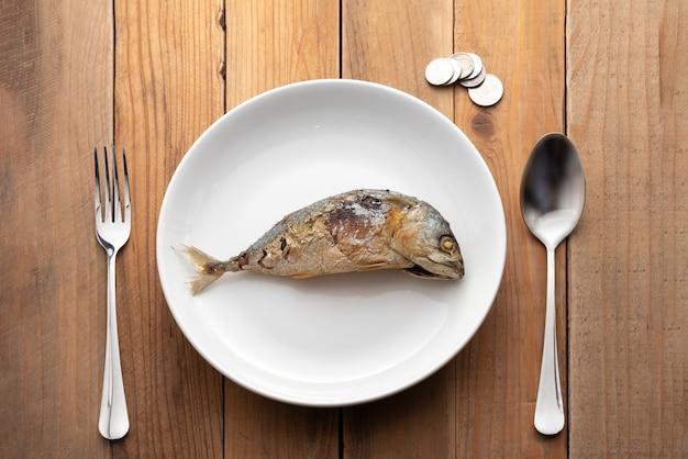 スプーン、フォーク、コインでプレートに表示される魚のサバ Premium写真